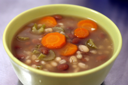 bowl of bean and barley soup with carrots and celery