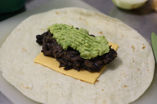 Cheese, black beans, and guacamole being wrapped in a tortilla.
