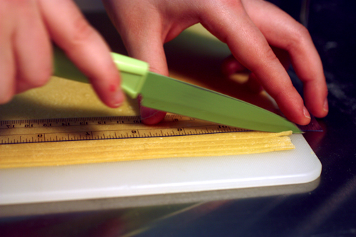 pasta being hand cut using a ruler's edge on a cutting board