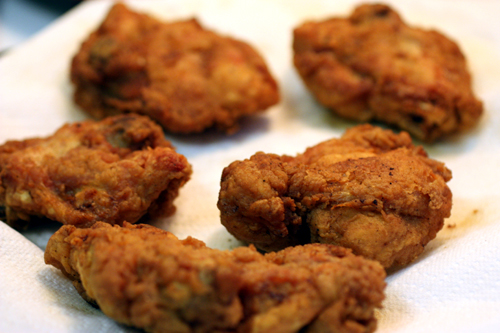 Chicken freshly fried and draining on paper towel
