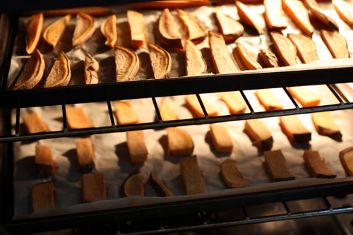 Sweet potato wedges roasting in the oven, spaced out evenly on two cookie sheets
