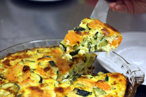Lifting out a triangle shaped slice of Kusa Jibben, Syrian style quiche with zucchini and carrots