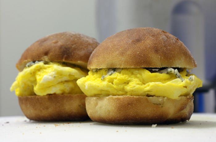 Two buns with egg and blue cheese sandwiched in the middle of each