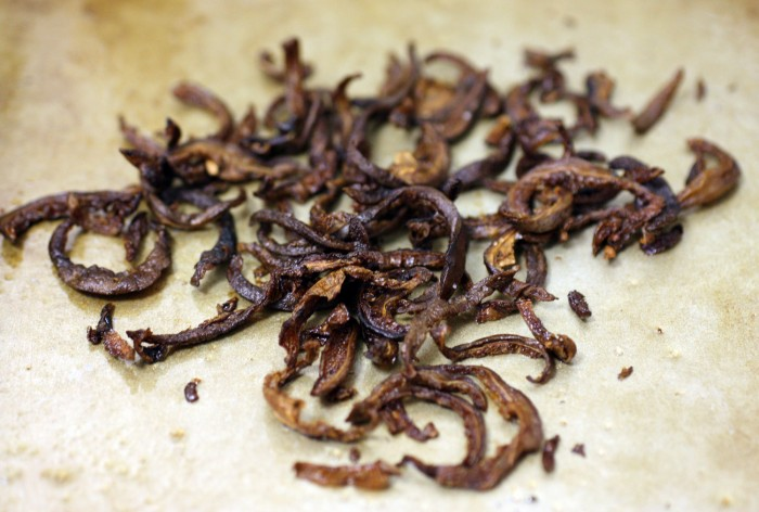 Crispy roasted shiitake mushroom strips on a metal baking sheet