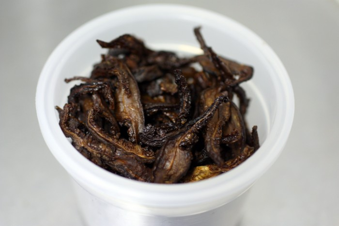 Crispy roasted shiitake mushroom strips in a small round tupperware